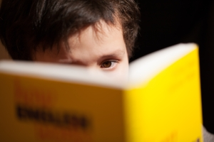 Young boy concentrating on reading a book with just his eyes visible over the top as he studies for class